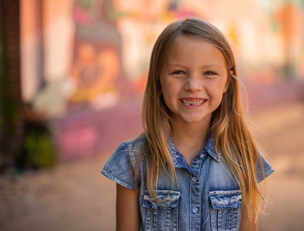 Young girl smiling with Invisalign aligners