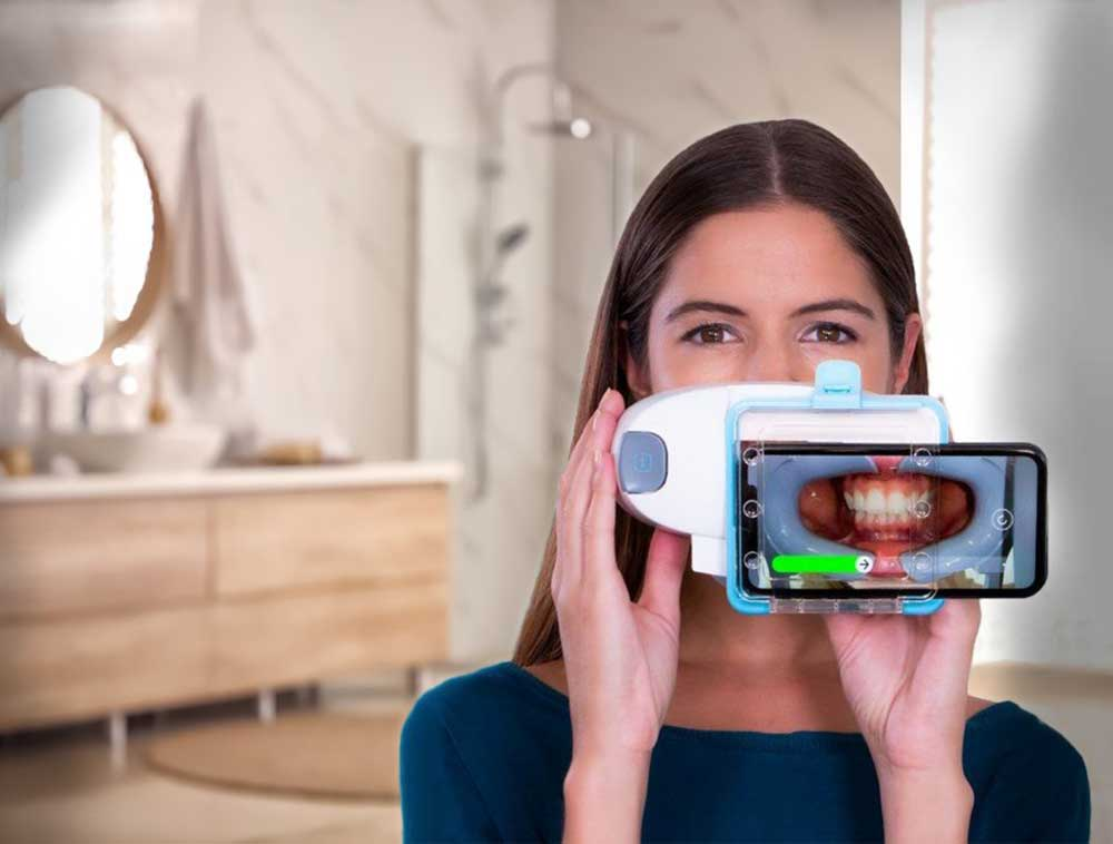 Invisalign patient scanning her smile for her orthodontist feedback.