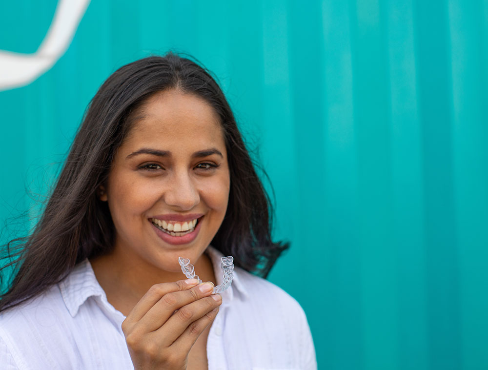 Hispanic woman smiles with Invisalign clear aligners.