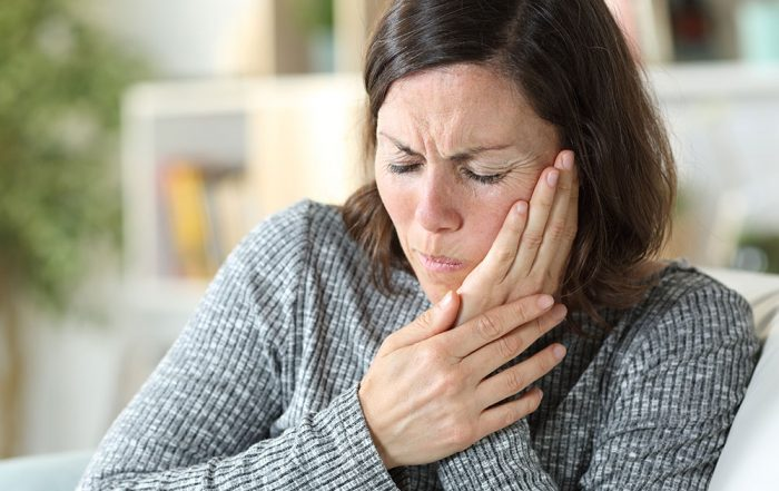Middle aged woman holding her TMJ in pain.